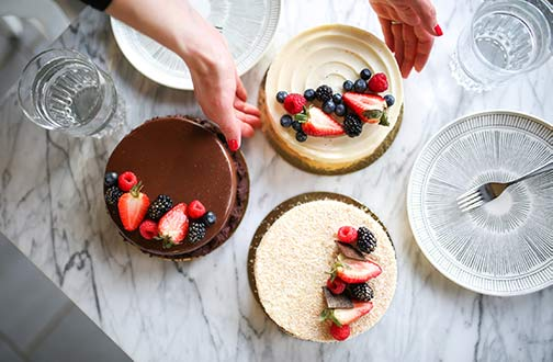 Three cakes photographed from above on a marble table, with hands reaching out to grab one cake. One cake is chocolate, another is coconut, and another is carrot cake. All three cakes have berries arranged artfully on top.