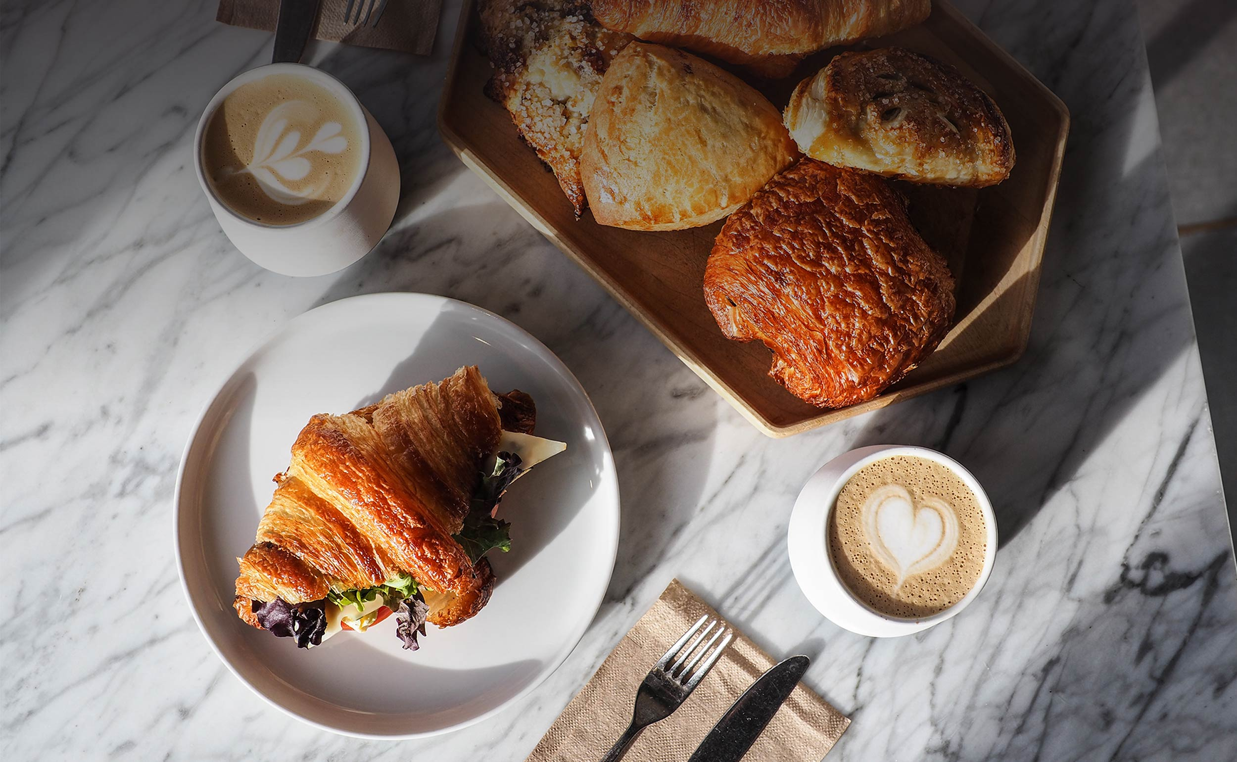Top down view of a marble breakfast table, with a breakfast croissant, lattes with latte art, and a geometric wood tray with an assortment of pastries: pain au chocolate, apple turnover, scones, and a plain croissant.