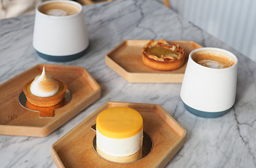 Marble table set with two lattes and an assortment of pastries: mini lemon meringue, mini frangipane, and mini passionfruit cheesecake.